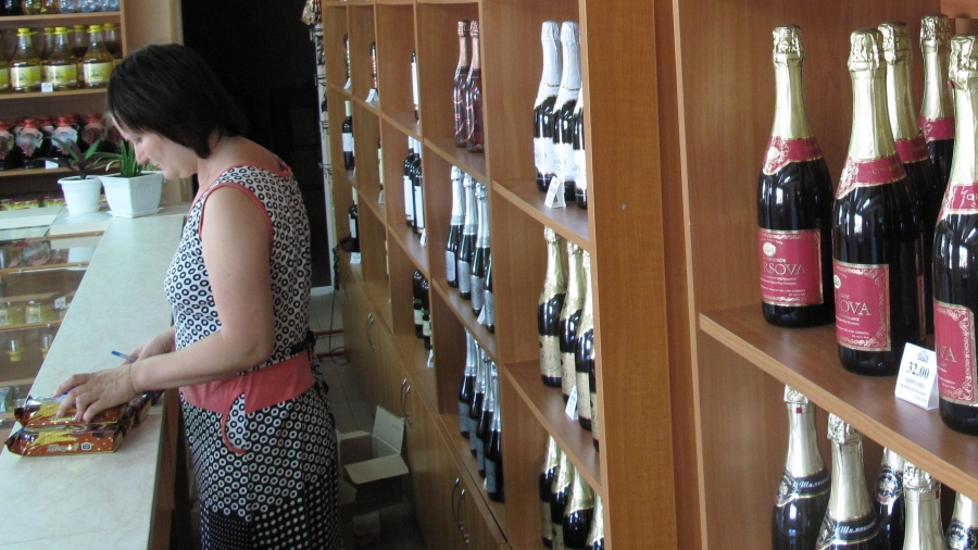 A saleswoman at the Chirsova winery shop in Gagauzia The winery is one of five vineyards exempted from Moscow's embargo on Moldovan agriculture products, but its owner is still worried about the region's economic future.