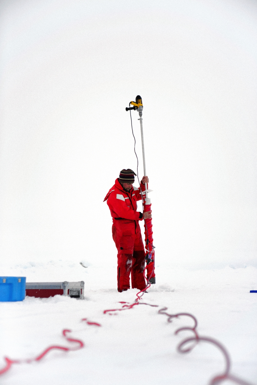 Chris Polashenski uses an electric drill to core out a sample of sea ice. He uses the cores to investigate the tiny cracks in the ice that may or may not allow water to drain from melt ponds