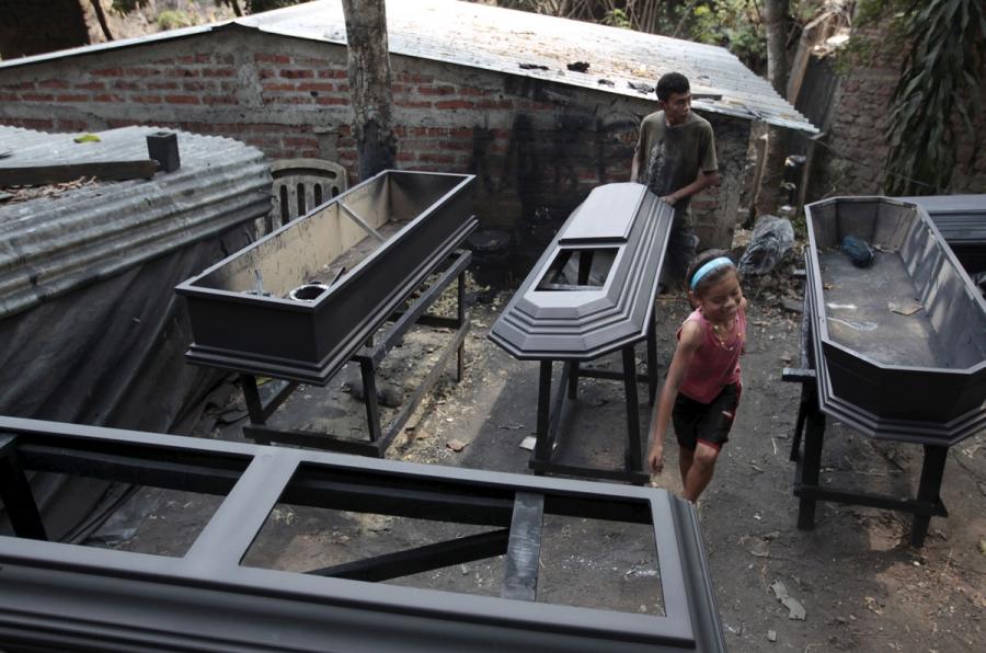 A worker applies sealant to a coffin at El Nuevo Renacer factory in Jucuapa.