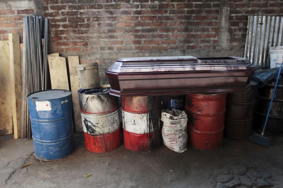 A coffin lies on barrels at El Nuevo Renacer factory in Jucuapa.