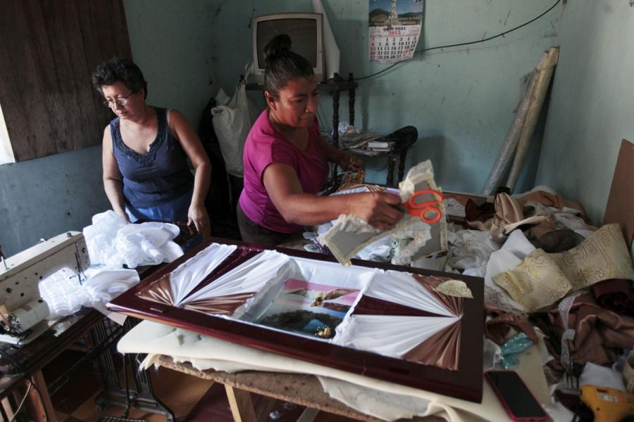 Women work on details of a coffin at El Nuevo Renacer factory in Jucuapa.