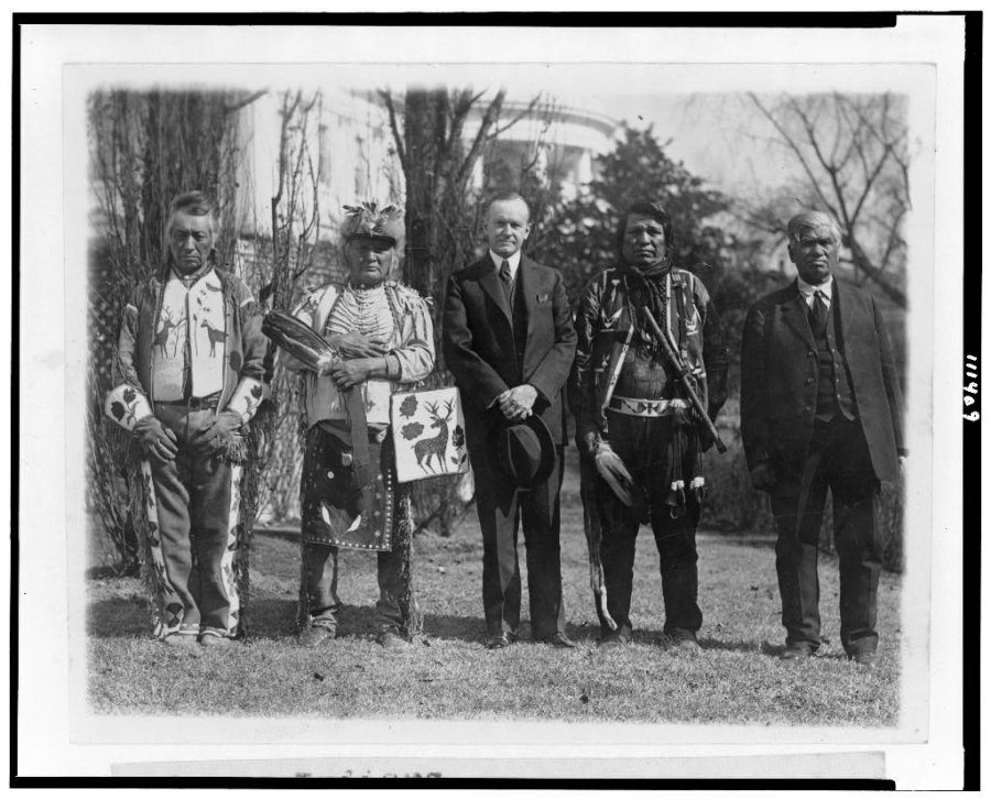 President Calvin Coolidge stands in front of the White House with four Native Americans, one of whom is dressed in suit, tie and vest, and the others wearing traditional dress.