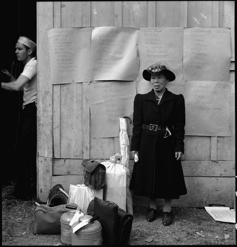 An elderly woman stands in front of posted signed with lists of Japanese names, luggage at her feet. A white man on the left.