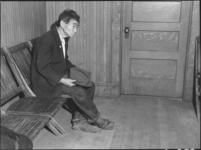 An elderly man sits on a bench