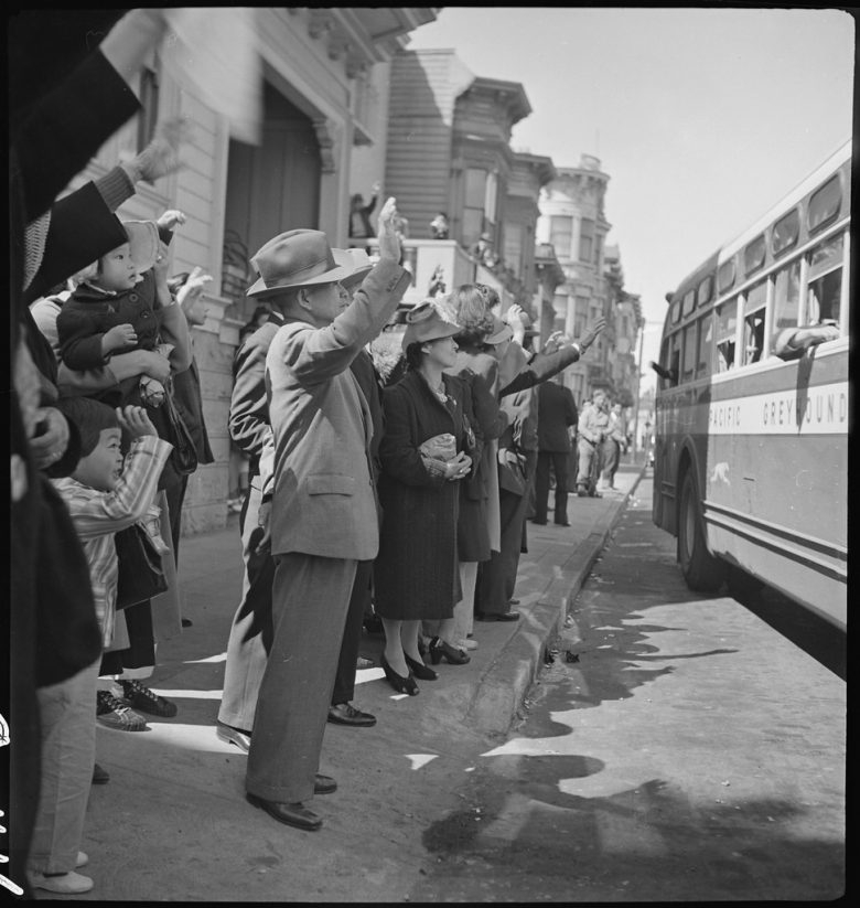Men and women stand on a sidewalk, waving at a departing Greyhound bus