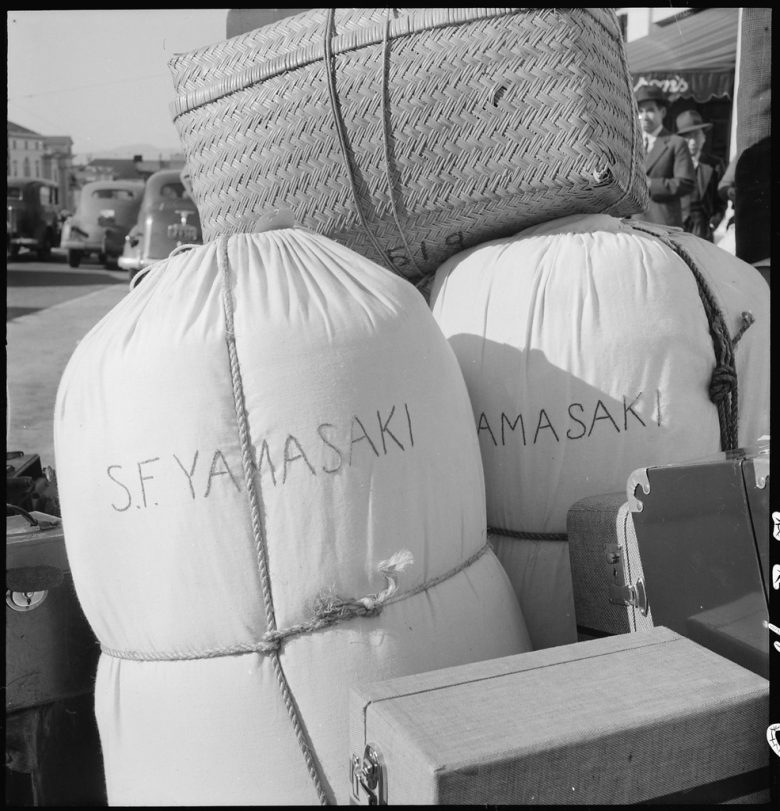"""Two bedrolls, luggage and a large box. Names on the side of bedrolls read """"S.F. Yamasaki"""""""