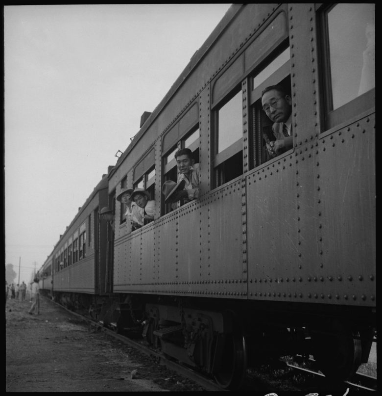 Men look out the windows of train cars