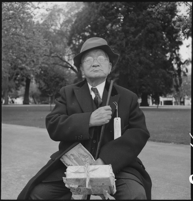 A man sits in a fedora and suit