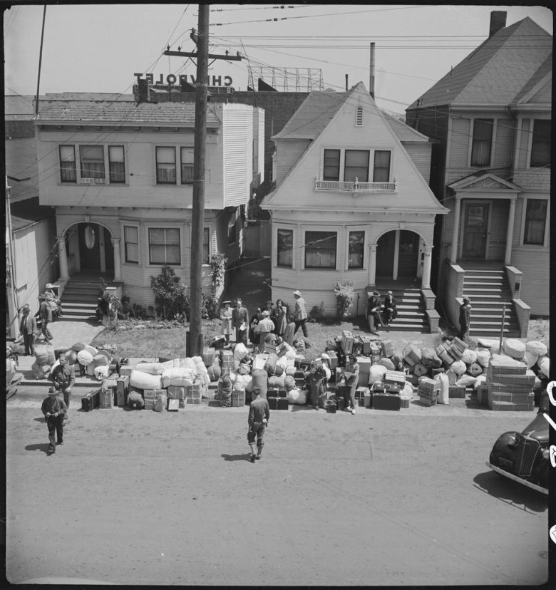 Luggage lines a street of two-story homes as families wait in front yards
