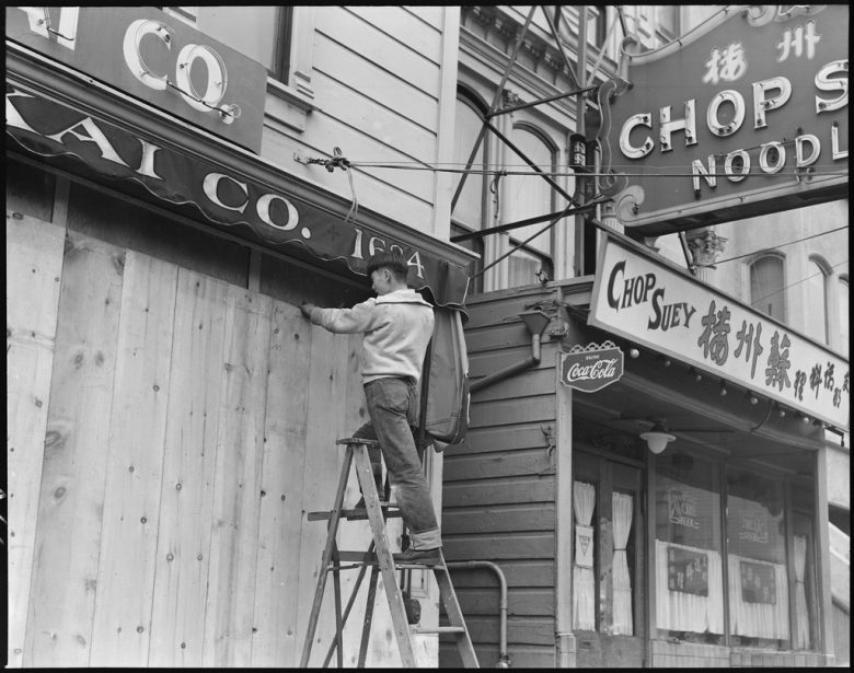 A man on a ladder installs boards on a shopfront