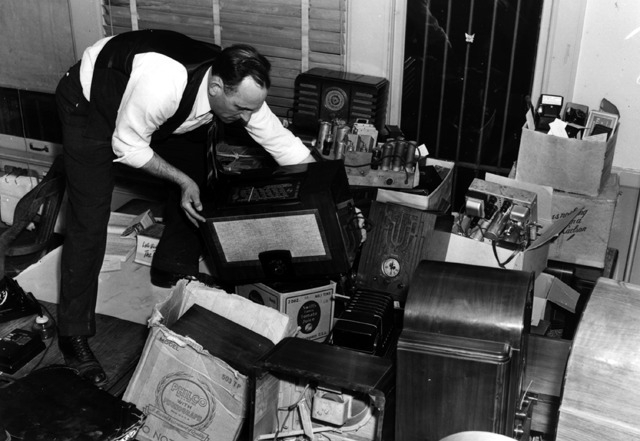 Black and white image of man go through a pile of cameras and radios