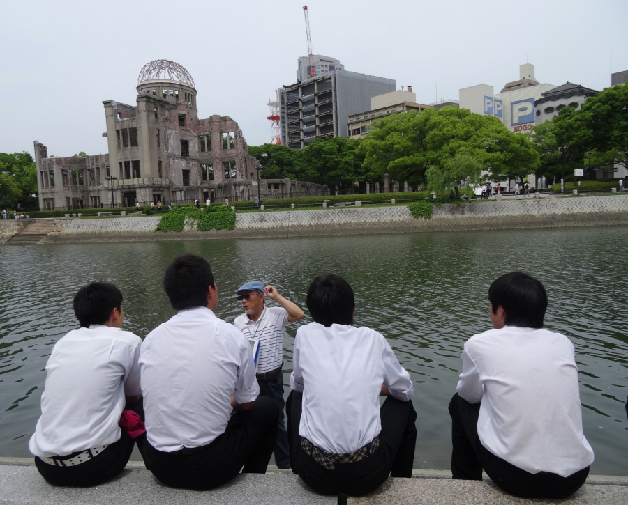 A volunteer guide speaks to school students across the river from the Atomic Bomb Dome in Hiroshima's Peace Memorial Park.