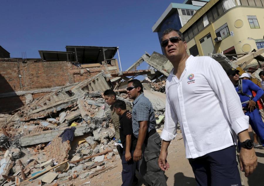 President Rafael Correa walks past a collapsed building