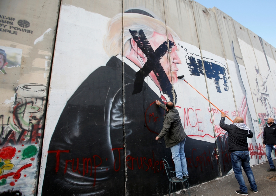 Men paint over a mural depicting US President Donald Trump painted on a part of the Israeli separation barrier, in the West Bank city of Bethlehem, Dec. 7, 2017.
