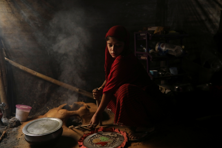 Shofika Begum cooks inside their temporary shelter at the Kutupalong refugee camp.