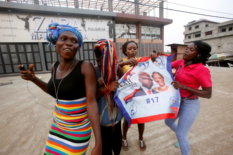Supporters of George Weah, former soccer player and presidential candidate of Coalition for Democratic Change (CDC), celebrate after the announcement of the presidential election results in Monrovia