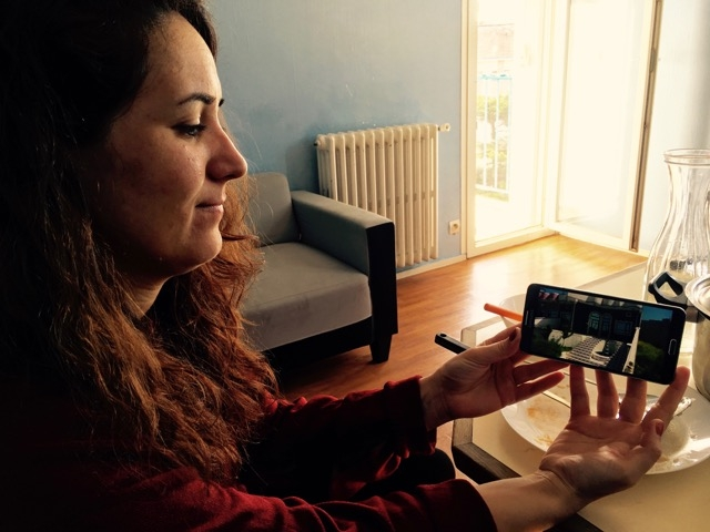Inside the Nohs' apartment in Saint-Nazaire, Suham Noh shows a photo of the family home they had to flee in the Sinjar region of Iraq.