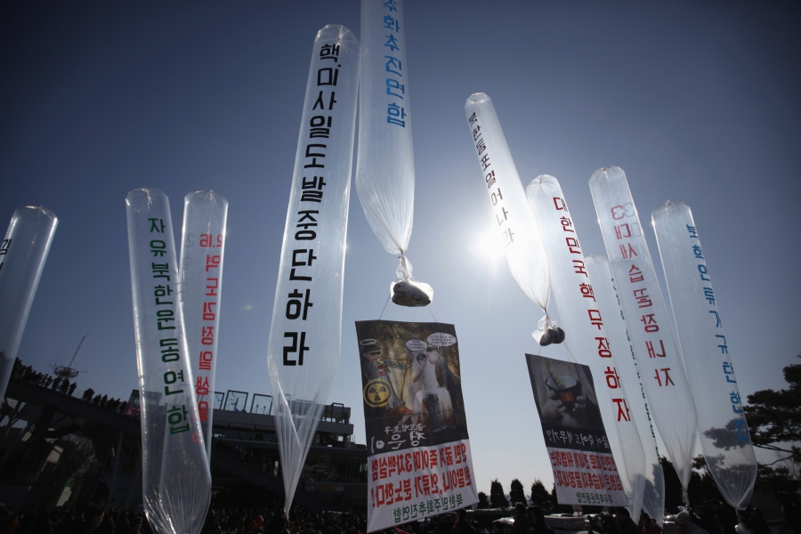 North Korean defectors living in South Korea hold balloons containing leaflets and CDs