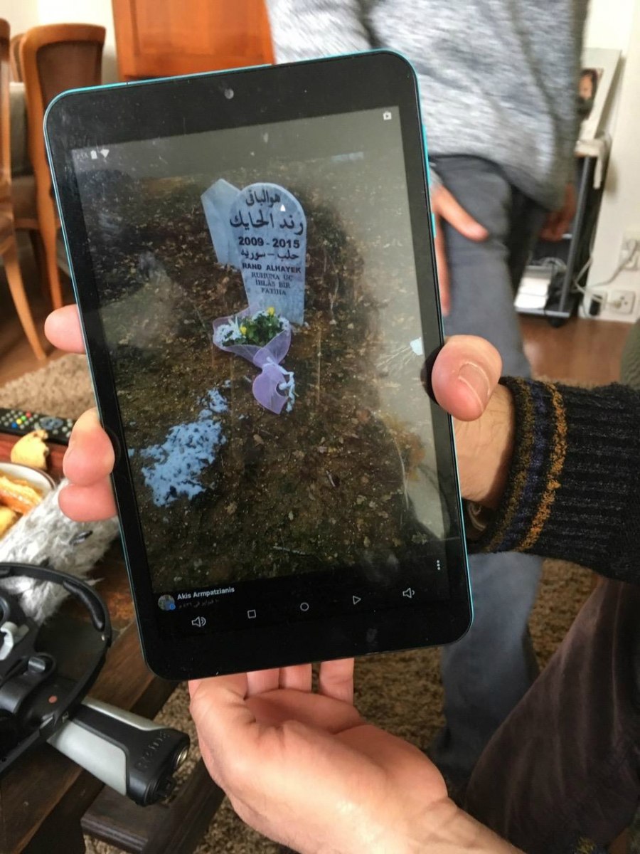 Mahmoud al-Hayek shows a photo of his daughter Rand's gravestone in Greece. Rand, 6, was killed by a train after the family crossed from Turkey into Greece as refugees.