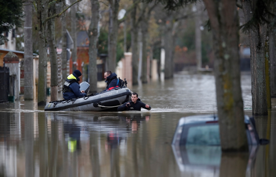 Paris police divers use a small boat to patrol a flooded street of a residential area in Villeneuve-Saint-Georges, near Paris.
