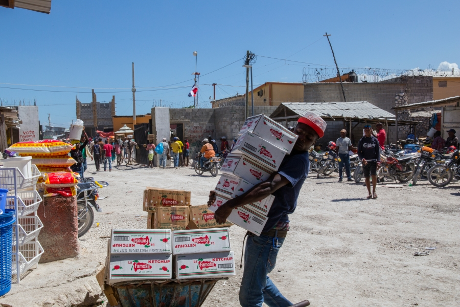 A man loads up a wheelbarrow with Dominican catsup on the Haitian side of the border.