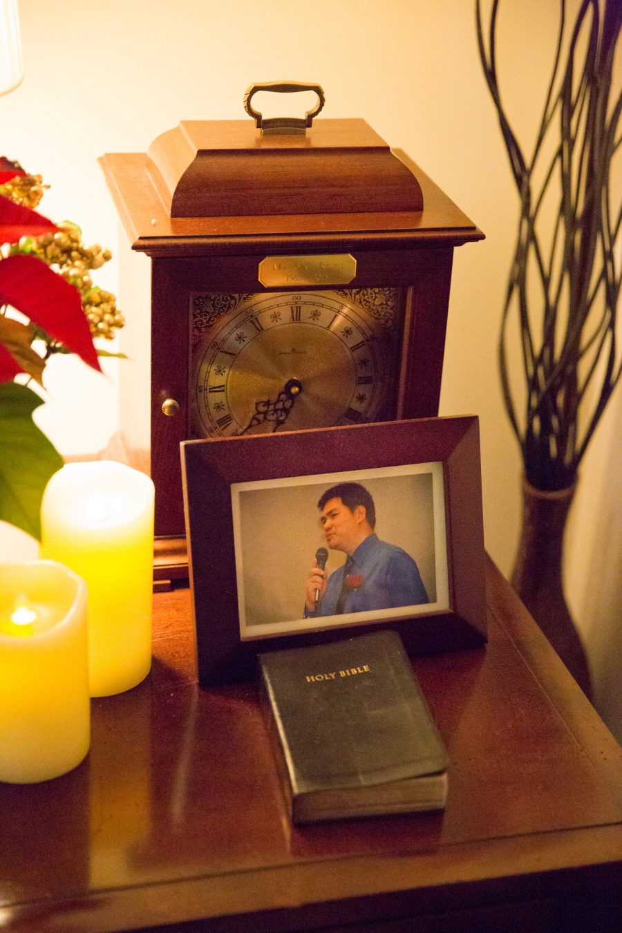 A framed photo is on top of a table with an unopened bible.