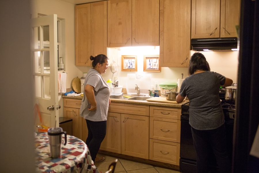 Two woman standing at counter in kitchen, photographed through doorway behind them