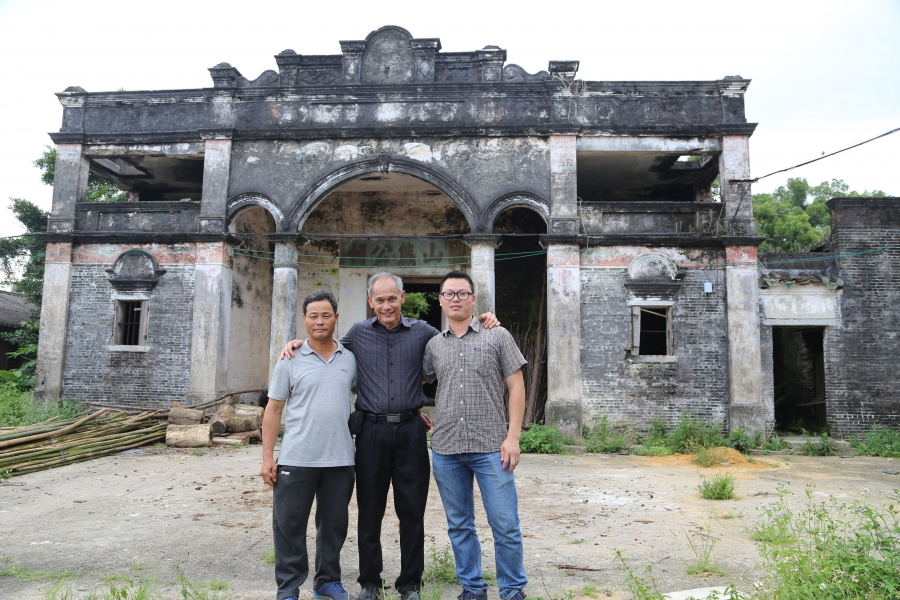 Three men stand in front of an old home.