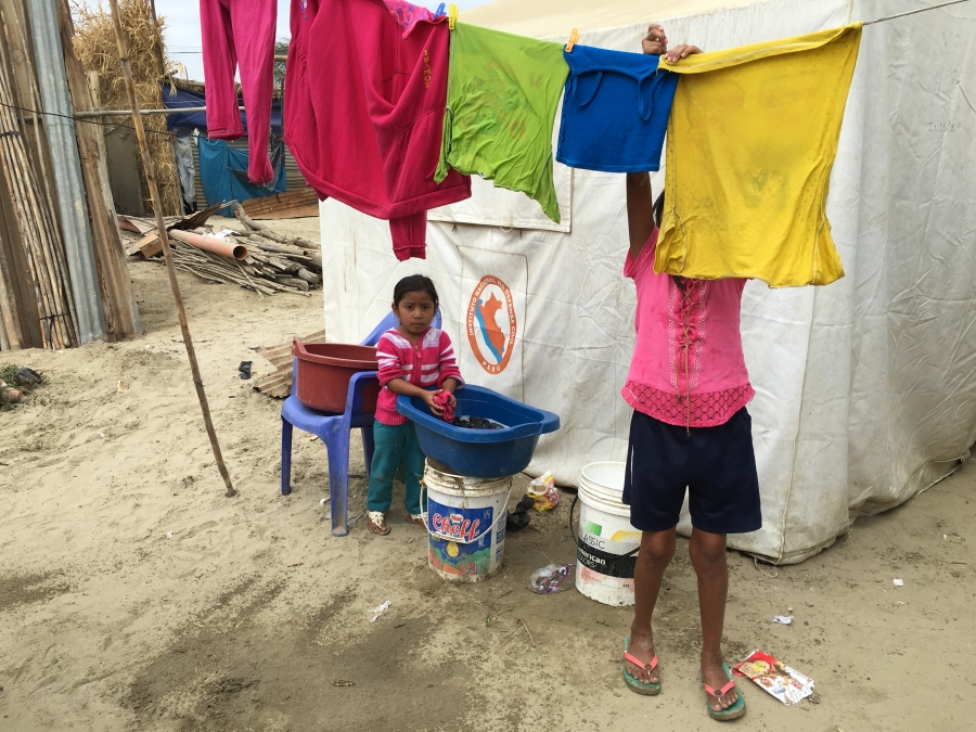 Children hang clothes to dry outside their tent on a clothsline in the village of Pedregal Chico.