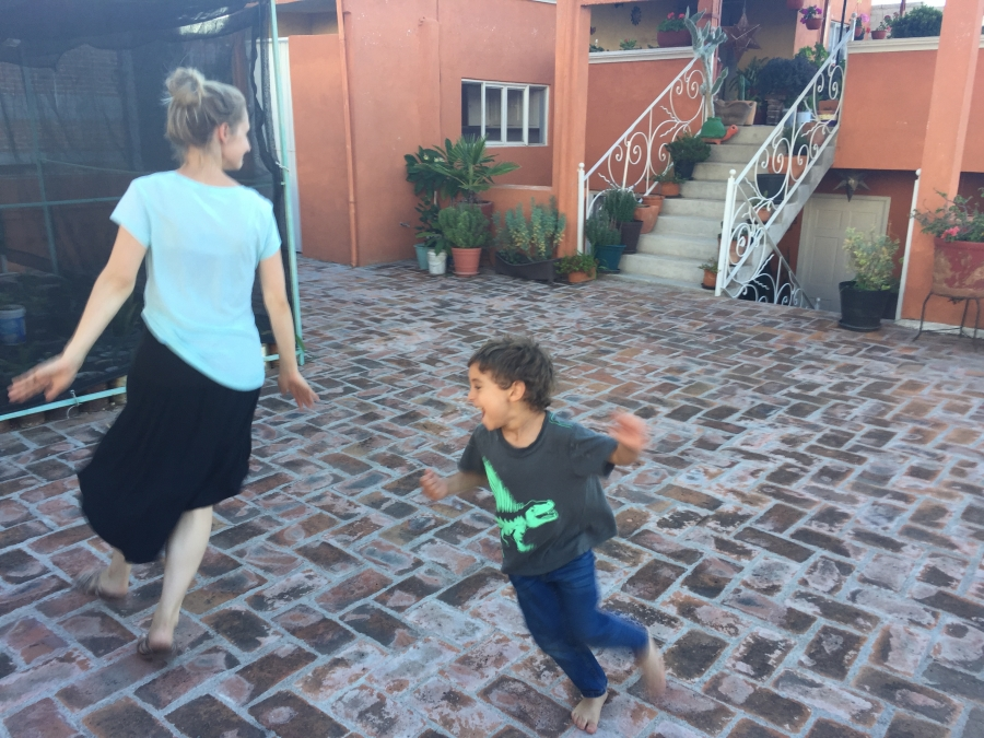 Young boy chases woman on cobblestone terrace