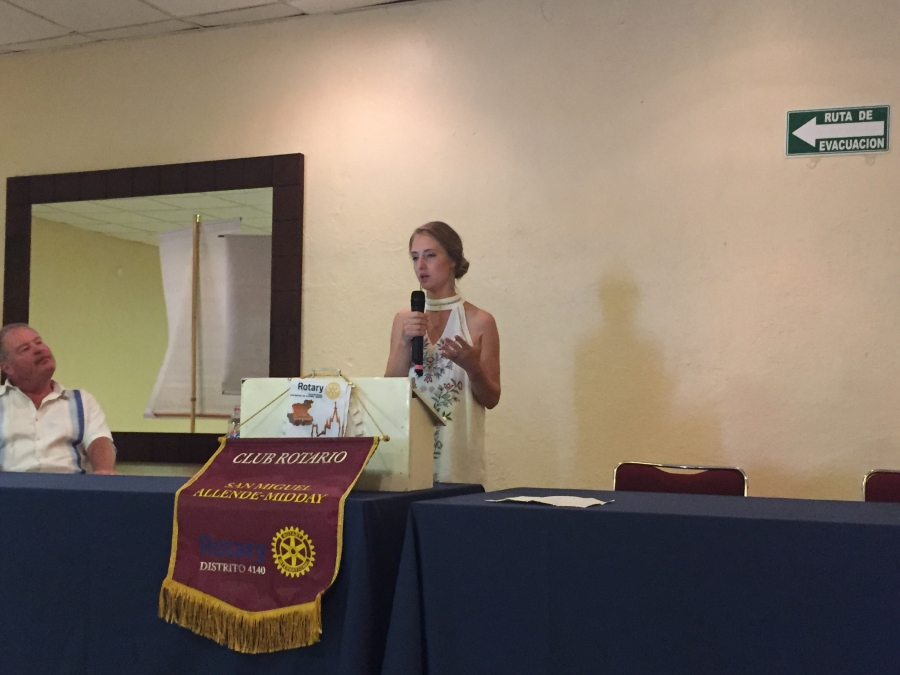 Woman in white dress stands behind podium Rotary Club emblem, holding microphone