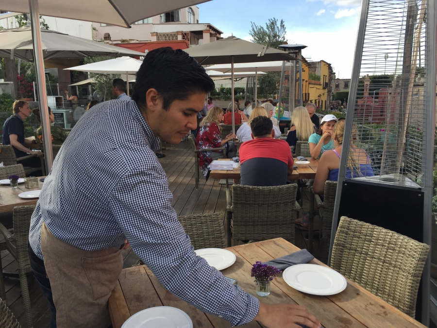 Man setting dishes on table in outdoor restaurant, with customers at table behind