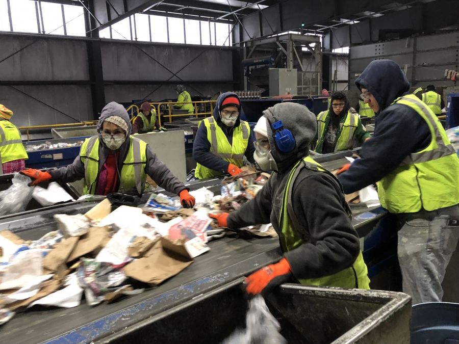 Workers manually sort trash from recycling at E.L. Harvey & Sons. Approximately 15 percent of the recycling that's collected here is unusable trash.