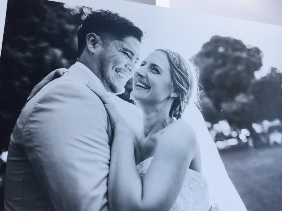 photo of a black and white photo of bride in white gown and groom, smiling