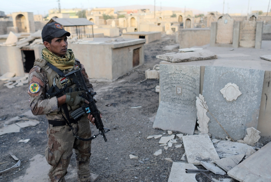 An Iraqi special forces soldier stands in a Christian cemetery damaged by ISIS fighters in Bartella, east of Mosul, Iraq, Oct. 21, 2016.