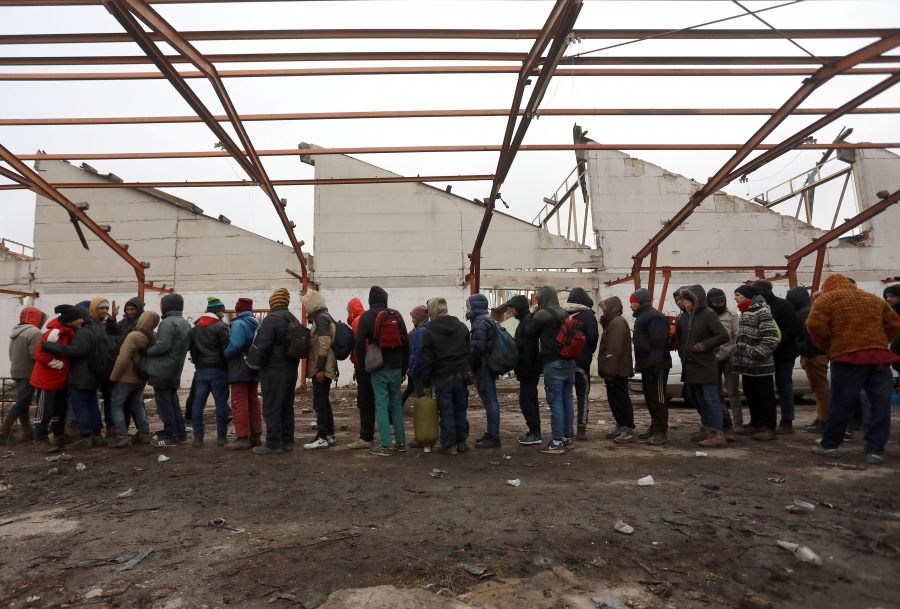 Migrants wait to receive food inside an abandoned factory close to the Croatian border near the town of Sid, Serbia, Dec. 19, 2017. Thousands of migrants and refugees remain stranded in the country. Iraqis and Syrians have the best chances of being grante