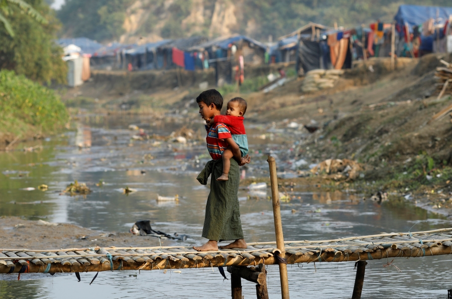 A Rohingya refugee child, carrying another child, walks along a bridge from no-man's land to Bangladesh, at the Bangladesh-Myanmar border near Cox's Bazar, Bangladesh, Jan. 12, 2018.