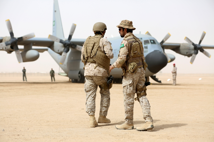 Saudi soldiers walk past a Saudi air force cargo plane delivering aid at an airfield in the northern province of Marib, Yemen, Jan. 22, 2018.