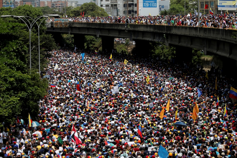 """Demonstrators march during the so-called """"mother of all marches"""" against Venezuela's President Nicolas Maduro in Caracas, Venezuela, April 19, 2017."""