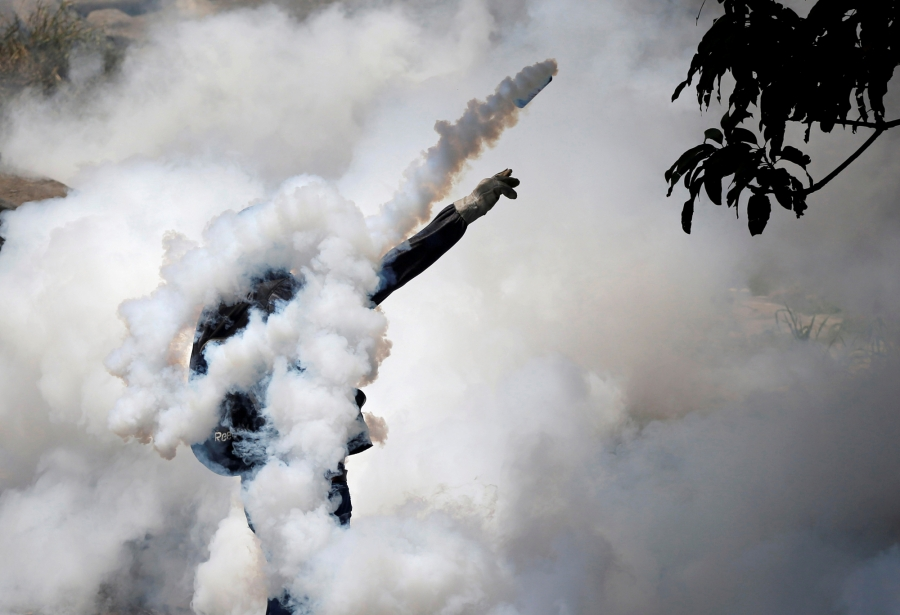A demonstrator throws back a tear gas grenade while clashing with riot police in Caracas, Venezuela, April 19, 2017.