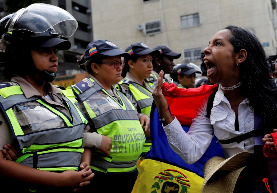 A demonstrator shouts slogans in front of police officers during a women's march in Venezuela