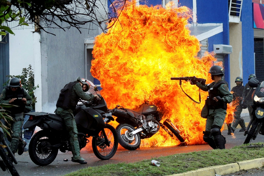Riot security forces clash with demonstrators as a motorcycle is set on fire during a protest against Venezuelan President Nicolas Maduro's government in San Cristobal, Venezuela, May 29, 2017.