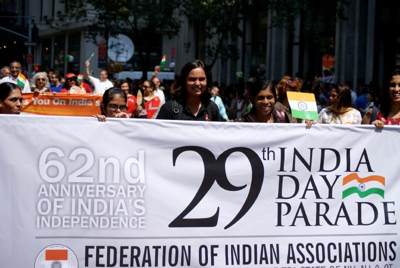 "Woman stands in crowd behind sign that reads ""29th India Day Parade"""