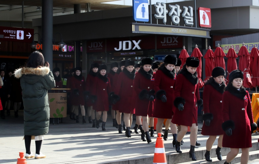 Members of North Korean cheering squad, dressed in red knee length jackets with black fur trim, walk at an expressway service area in Gapyeong, South Korea, Feb. 7, 2018.