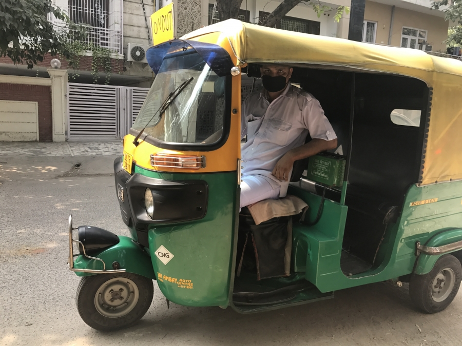 """Imran Khan, a local """"autowallah"""" — a driver of a motorized three-wheel passenger vehicle — wears a mask to protect himself from polluted air. Khan tries to get more autowallahs to wear masks, too, but few have followed his lead."""