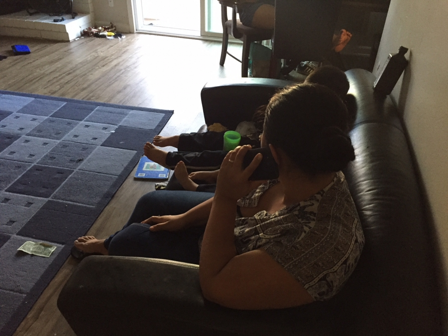 Woman on phone sitting on sofa, with kids next to her