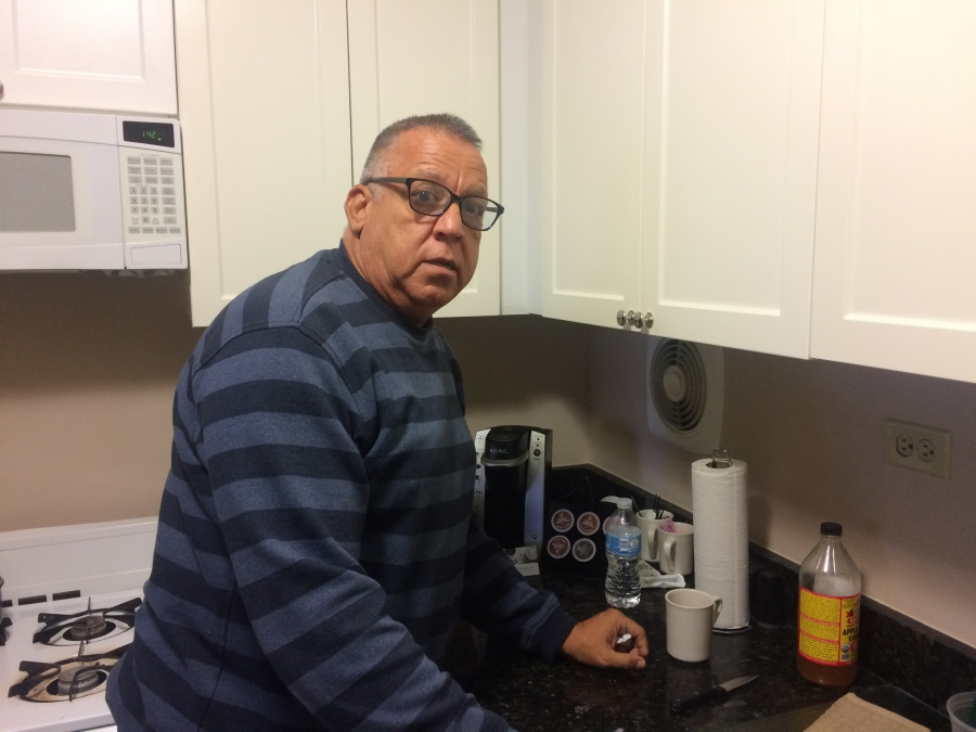 Carlos Torres makes coffee in the kitchen of his hotel room.