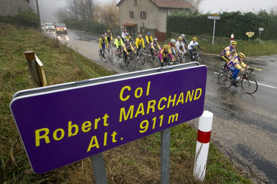 Robert Marchand (R), 103 years-old, cycles in the rain ahead of a small group of riders to celebrate his birthday as he makes his way along the Robert Marchand pass