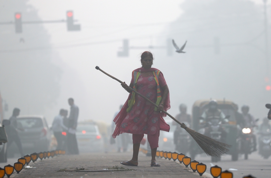 A street cleaner works in heavy smog in Delhi, India, Nov. 10, 2017.