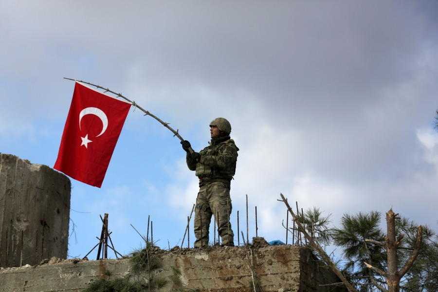A Turkish soldier waves a flag on Mount Barsaya, northeast of Afrin, Syria, Jan. 28, 2018. Turkey and allied Syrian rebel groups have opened a new front in Syria's multisided war with an assault on the territory against the US-backed Kurdish militia, the
